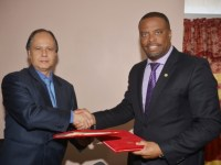 Minister Brantley (right) and H. E. Vasconcellos (left) exchange signed documents