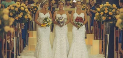 the triplet sisters walking down the aisle in similar wedding dresses, makeup, and hairstyles