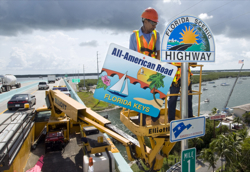 Rudy Nichols, a Florida Department of Transportation sign crew leader, positions a placard designating the Florida Keys Overseas Highway as an All-American Road, the highest national recognition a roadway can receive.