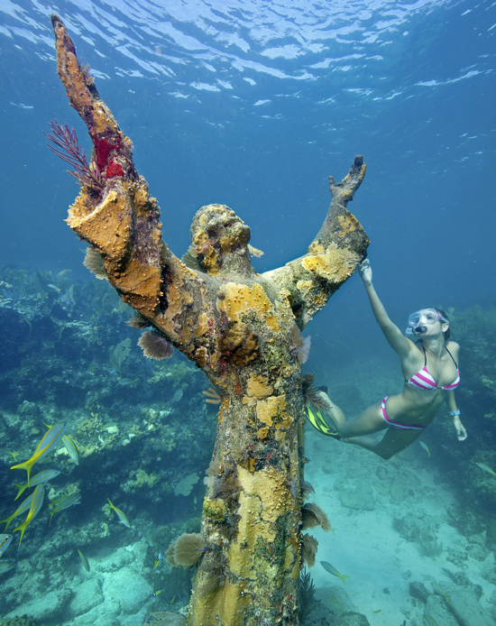 """Katherine Wieland snorkels by the the """"Christ of the Abyss"""" statue, an underwater icon for John Pennekamp Coral Reef State park, off Key Largo, Fla. Named after a former Miami newspaper editor, Pennekamp is the nation's first underwater preserve and is to celebrate its 50th anniversary Dec. 10, 2010. (Photo by Stephen Frink/Florida Keys News Bureau"""