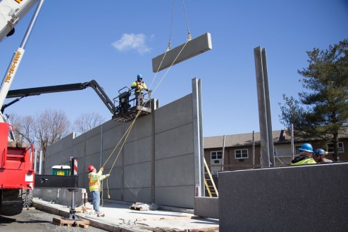 March 29, 2017 - Workers guide the placement of a precast concrete panel.