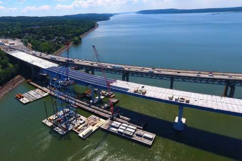 August 3, 2016 - Crews place prefabricated road deck panels on the Westchester approach.