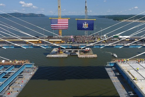 August 24, 2017 - The US and New York State flags hang from barge-based cranes at the main span.