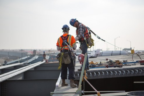 December 11, 2015 - Construction workers tethered to safety harnesses near a newly installed road deck panel.
