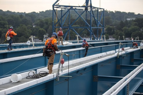 July 22, 2016 - Workers equipped with fall protection harnesses navigate across the bridge's structuralsteel.
