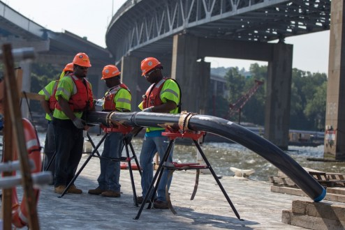 July 22, 2016 - Crew members assemble conduits for the new bridge's electrical system on a temporary work platform.