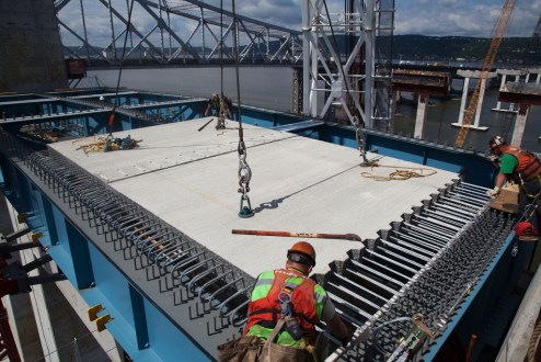 June 29, 2016 - Crews install a precast road deck panel atop a section of main span steel.