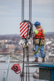 March 10, 2016 – An ironworker waits atop a steel girder as a nearby crane raises another section of structural steel.