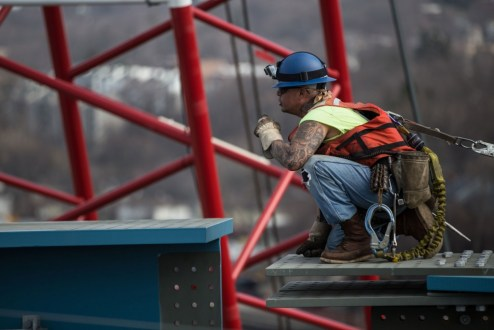 March 10, 2016 – An ironworker helps guide a new steel girder segment to its final position.