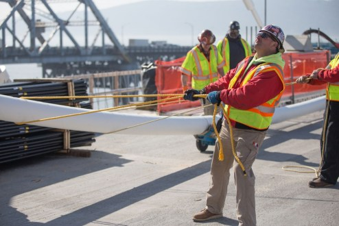 February 23, 2017 - Workers help guide a stay cable as its raised to an anchor point on the iconic main span towers.
