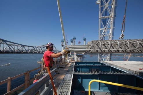 September 14, 2016 - A worker helps guide the placement of a concrete road deck panel on the main span.