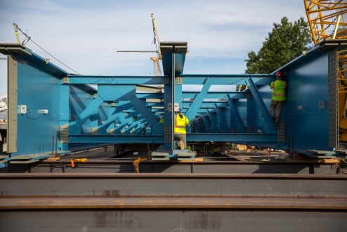 September 25, 2015 - Workers prepare a massive steel-blue girder assembly for installation from the Westchester abutment.