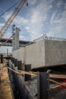 May 5, 2015 - Precast concrete pier caps are stored on nearby barges before their installation atop the pier columns, pictured in the background.