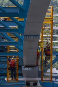 June 30, 2015 - Ironworkers inspect their work after the installation of one of the new bridge's massive girder assemblies.