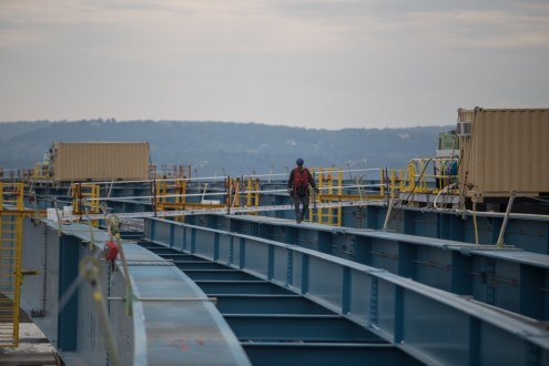 July 21, 2015 - A worker carefully navigates across the new bridge's steel girders.