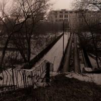 """Tiltas per Vilnelę šalia fabriko. Matosi pusiau apleistos buvusios valstybinės Vilniaus elektros matavimo technikos gamyklos """"Skaiteks"""" pastatai."""