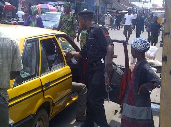 Lagos police officer tugging passenger