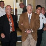 Jerry Sandusky, hands shackled, is whisked off to county jail.