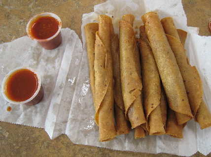 Rolled tacos and hot sauce