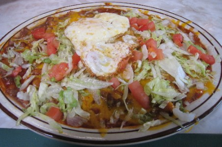 Blue corn tortilla enchiladas topped with a fried egg
