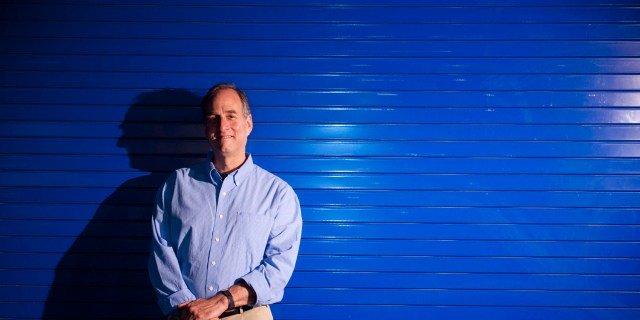 Dan Distel standing in front of blue background