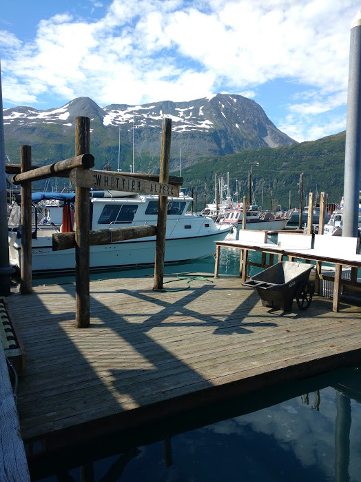 A photo of a mountain behind some boats in Whittier, Alaska.