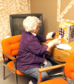 Volunteer Judy Givens stamps circulars for the mission.