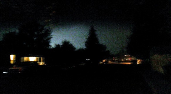 Lights from a Friday night high school football game shine through smoke settling over Williams.