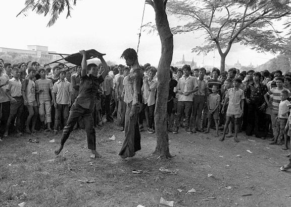 Un individuo golpea con una silla plegable el cadáver de un estudiante tailandés colgando de un árbol. La masacre cumple 40 años este 6 de octubre (AP)