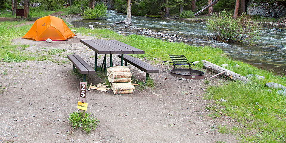 Finding and Setting Up a Campsite   Camping  U S  National Park Service  A campsite with a site marker  picnic table  fire ring  firewood and an