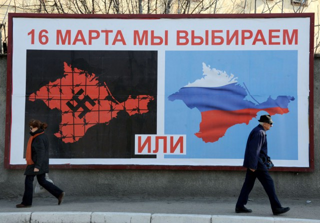 "People walk past a poster in Sevastopol on March 11, 2014 reading ""On March 16 we will choose either... or..."", depicting Crimea in red with a swastika and covered in barbed wire, and Crimea with the colors of the Russian flag. Pro-Moscow lawmakers in Crimea voted for independence from Ukraine on March 11 in a precursor to a referendum this weekend for the region to become part of Russia (Photo: Viktor Drachev)."
