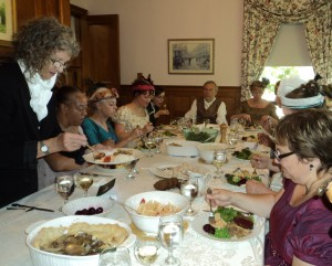 guests in Regency attire seated around a dining table