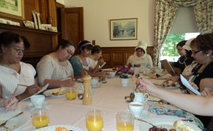 guests around the breakfast table writing answers for the Regency quiz