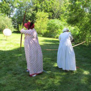 two ladies in Regency gowns practice their archery at the Jane Austen weekend