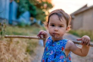 Little and dirty girl with her stick