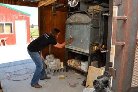 LaBar carefully removes the plug to view the pieces within the kiln.