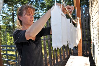 Ribbons are dipped into wax and then thick, white paint and hung to dry outside Renee's studio. The hot Southern Oregon sun will dry the pieces intended for an exhibition./Sabina Poole