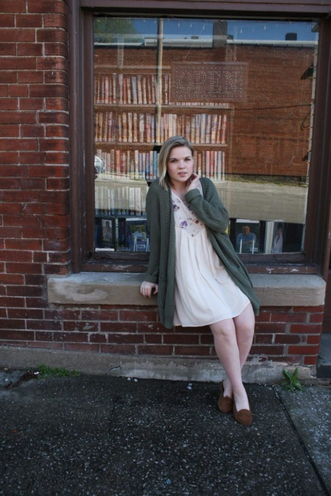 Philanthropy Dress. Modeling a cream dress with embroidered details, an oversized olive cardigan, and moccasins.