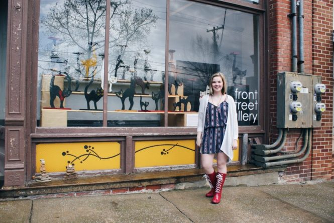 Clothes For a Cause. Modeling a printed romper, silver cardigan, and lace-up Roma boots in front of Front Street Gallery.