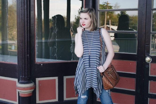 Modeling a navy striped tank top with denim, gold accessories, and a brown leather bag.