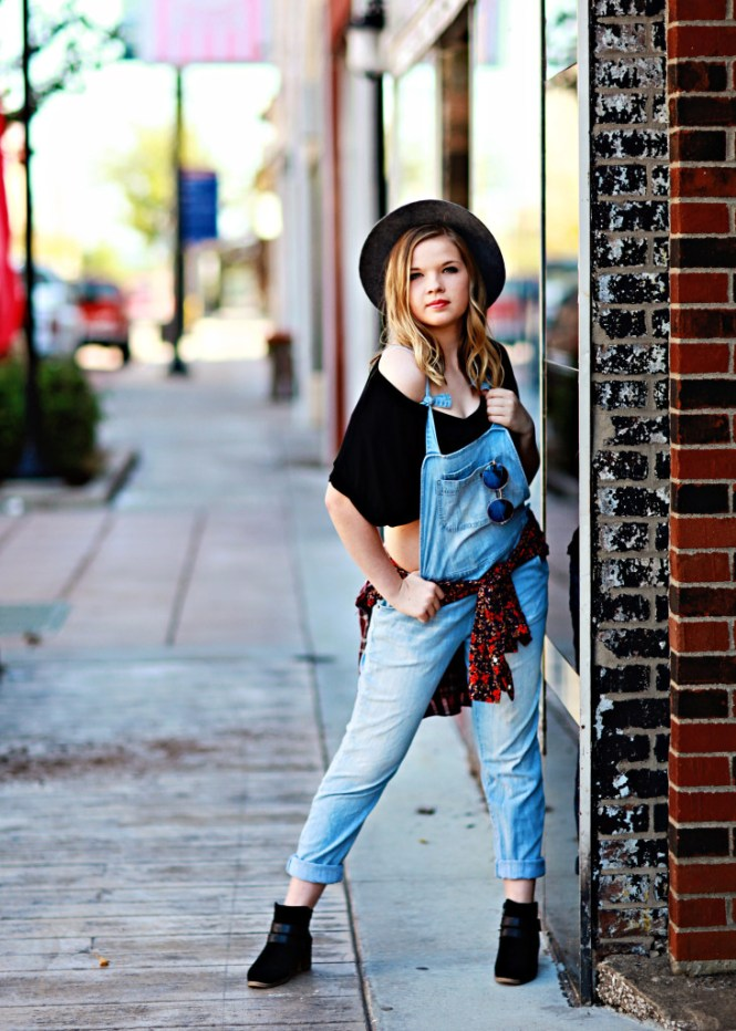 Senior Pictures: Style Guide. Modeling overalls and a crop top with a hat and flannel. Posing in downtown Cape Girardeau MO.