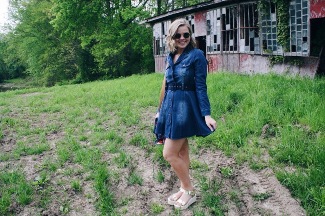I'm Feeling Inspired By The 70s. Modeling a pleated denim dress, platform sandals, round Ray-Ban sunglasses, and a printed Fossil purse.