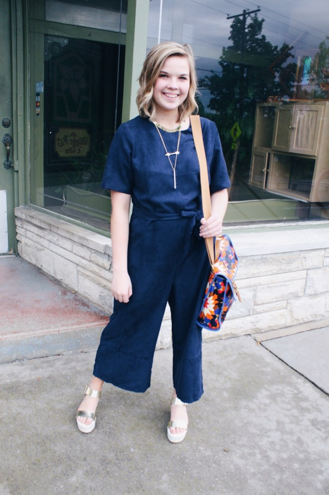A Jumpsuit and a CEO Trade Show. Modeling a navy jumpsuit, platform sandals, gold jewelry, and printed Fossil purse.
