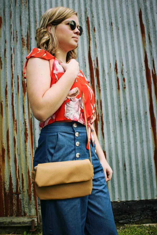 Being Bold In Floral, Blue, & Gold. Modeling a floral crop top, denim flare pants, gold accessories, and a neutral cross body.