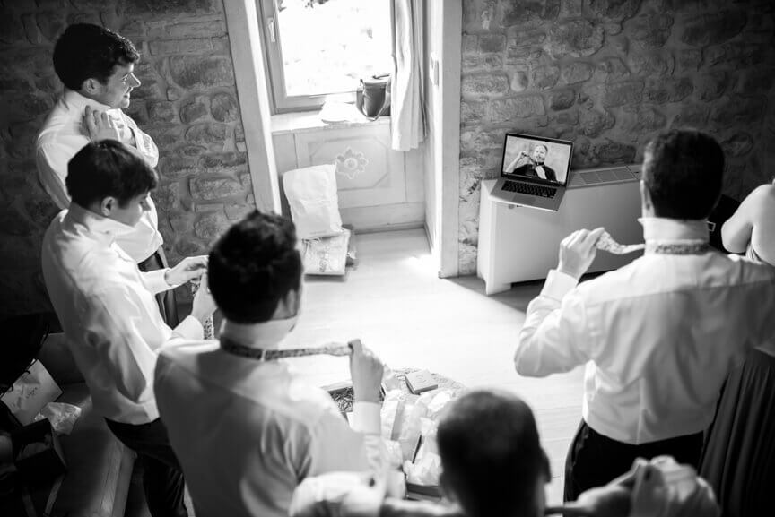 The groom and witnesses learn how to knit the tie