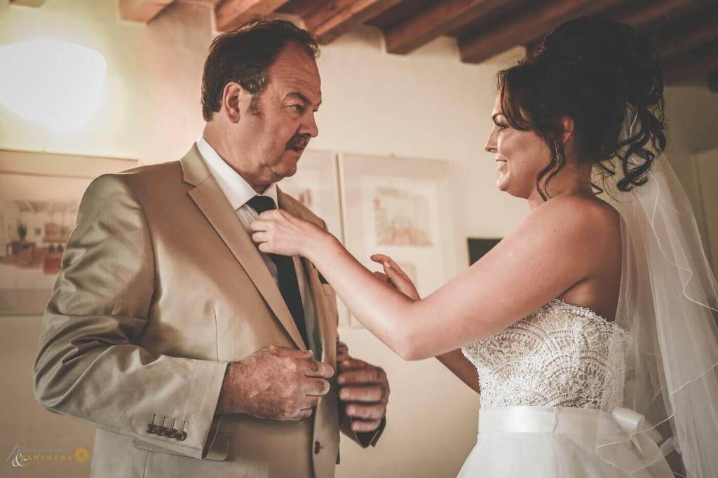 The bride fix up the tie to her father