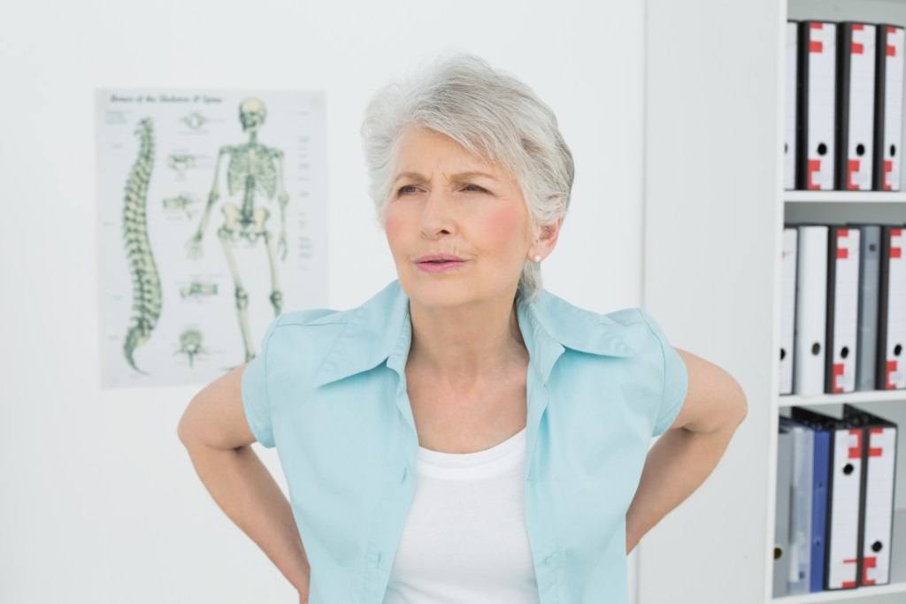 Senior woman with back pain in medical office
