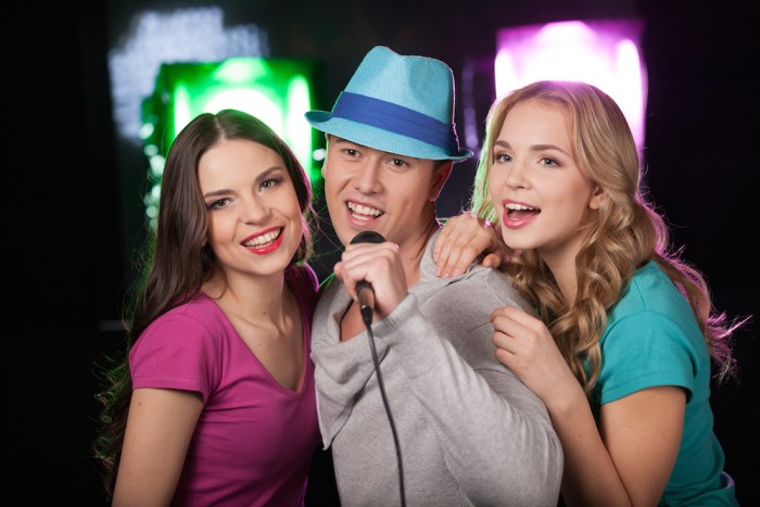 Group of three friends singing with microphone. man with blue hat standing on black background and singing