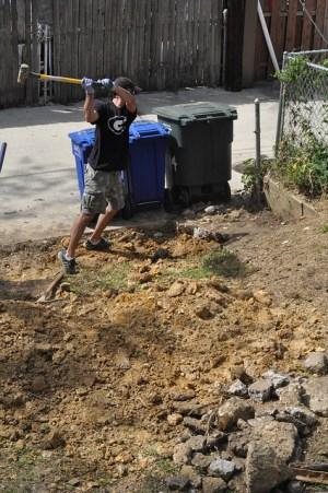 Sledgehammering concrete driveway backyard