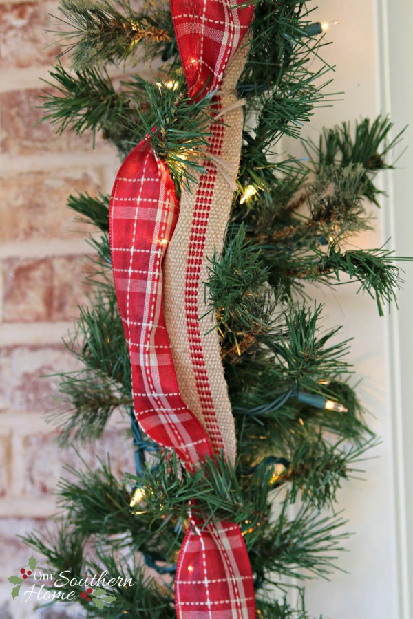 Plaid ribbon and upholstery ticking trim the door / Christmas Front Porch / www.oursouthernhomesc.com